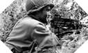 Image : Le soldat Sam J. Abbot avec sa mitrailleuse Browning en surveillance dans une haie du bocage
