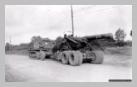 Image : Le 31 juillet 1944, un obusier M1 américain est tracté sur la route de Carantilly par un M4 High Speed Tractor appartenant à un Field Artillery Batallion.
