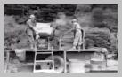 Image : 17 juillet 1944 : dans le secteur de Castillon, des sapeurs américains ont réussi à mettre au point une machine à laver de fortune avec les moyens du bord.