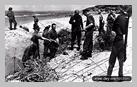 Image : Sur la plage de Deauville après les combats, des prisonniers allemands sous bonne garde déblaient les obstacles de plage et les réseaux de barbelés.