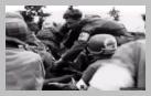 Image : 7 août 1944 : une française, qui a eu les deux jambes arrachées suite à l'explosion d'une mine anti-personnelle allemande, est emmenée jusqu'au poste de secours de la 79ème division d'infanterie américaine.