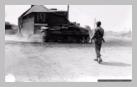 Image : Un policier militaire américain armé d'une carabine USM1 observe un char léger Stuart poursuivre sa progression dans le Tronquay