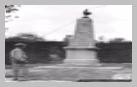 Image : 12 juin 1944 : un soldat américain observe le monument aux Morts de la Première Guerre mondiale sur la commune de Mosles.