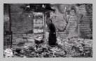 Image : 17 juin 1944 : une habitante d'Orglandes dans les vestiges de sa maison détruite par les bombardements.