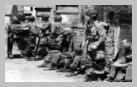 Image : Un stick commandé par le capitaine Kenneth Johnson de la HQ Company du 508th Parachute Infantry Regiment, 82nd Airborne Division, loin de sa zone de saut initialement prévue, progresse vers le sud le Jour J et marque une courte pause dans Ravenoville.