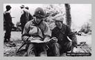 Image : 7 juin 1944 : un lieutenant appartenant aux Civil Affairs du 5ème corps américain s'entretient avec Gustave Joret, ouvrier agricole, au sujet des dernières positions allemandes connues. Ce dernier est blessé quelques heures après la prise de cette photo par le tir d'un soldat américain et meurt des suites de sa blessure le 12 juin 1944.
