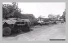Image : 1er juillet 1944 : une Jeep longe un convoi de véhicules allemands et un char Sherman détruits sur la route départementale 49 au lieu dit de La-Lande-des-Morts sur la commune de Trelly.