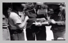 Image : 6 août 1944 : Marc Didier, habitant de Tribehou présente à des soldats américains un dispositif ingénieux de récepteur radio dissimulé dans une boîte de cigares.