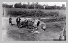 Image : 10 août 1944 : un père et sa fille habitant le secteur de Vengeons observent l'épave d'une Simca 8 détruite avec un soldat allemand tué à son bord.