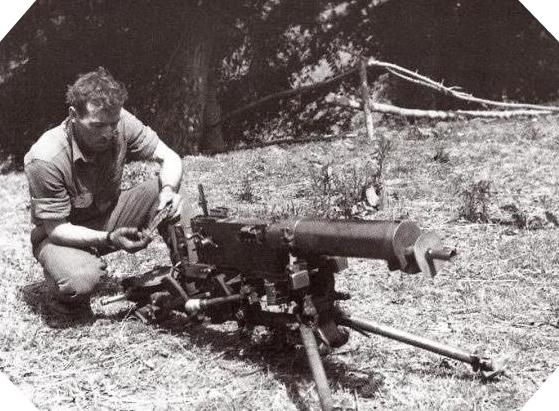 """Pendant la bataille de Normandie, le soldat de première classe Arland """"Pappy"""" Fry, spécialiste des armements appartenant à la compagnie A du 377th Parachute Field Artillery Battalion inspecte une mitrailleuse MG 08 sur trépied abandonnée par les Allemands dans la commune de Catz située à l'est de Carentan dans la Manche"""