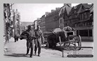 Image : 27 août 1944 : des soldats canadiens progressent à côté de deux charrettes allemandes dans les rues de Elbeuf.