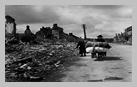 Image : 15 juin 1944 : des civils normands chargés par leurs biens transportables les plus précieux marchent le long d'une rue dégagée de la commune dévastée de Pont-l'Abbé.