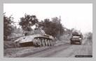Image : Un half-track roule à proximité d'un char Panther D détruit sur la route nationale 175 à hauteur de Tourville-sur-Odon.