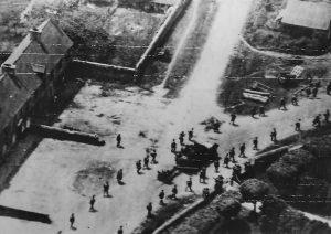 Des soldats américains appartenant au 39th Infantry Regiment de la 9th Infantry Division progressent en colonne double à travers le bourg de Saint-Jacques-de-Néhou, libéré le 17 juin 1944. Un half-track M3 tracte un canon antichar de 57 mm.