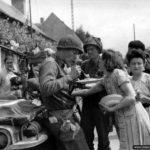 8 août 1944 : des soldats américains à côté d'une Jeep savourent un repas offert par la population de Champigné en liesse après sa libération. Il s'agirait du Captain Phillip C. Staples de la compagnie G, 2nd Infantry Regiment, 5th Infantry Division. Photo : US National Archives