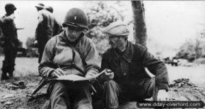 7 juin 1944 : un lieutenant appartenant aux Civil Affairs du 5ème corps américain s'entretient avec Gustave Joret, ouvrier agricole, au sujet des dernières positions allemandes connues. Ce dernier est blessé quelques heures après la prise de cette photo par le tir d'un soldat américain et meurt des suites de sa blessure le 12 juin 1944. Photo : US National Archives