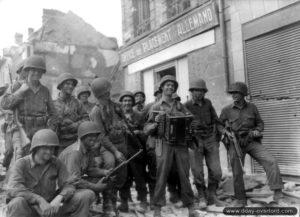Des soldats du 317ème régiment de la 80ème division d'infanterie américaine dans la rue Saint-Germain à Argentan, écoutent le soldat H. C. Medley jouer à l'accordéon. Photo : US National Archives