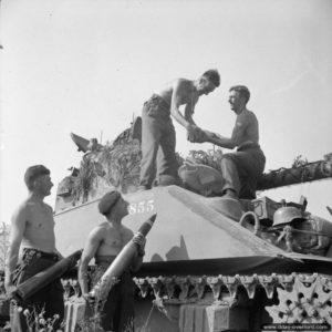 7 août 1944 : l'équipage d'un char Sherman Firefly du 1st Northamptonshire Yeomanry ravitaille en obus avant le lancement de l'opération Totalize dans le secteur d'Ifs. Photo : IWM